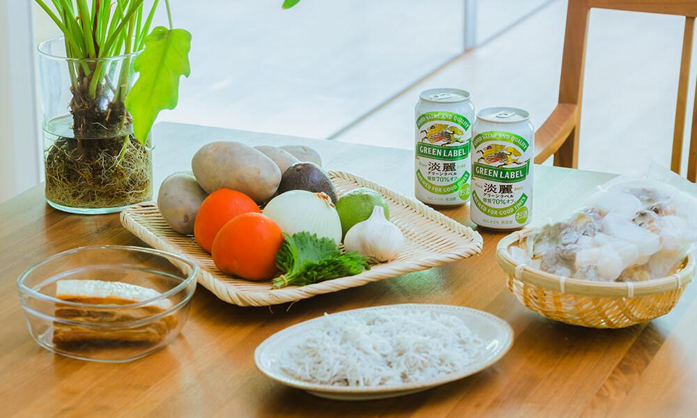 一桌豐富食材有冷凍綜合海鮮、馬鈴薯、培根、番茄、酪梨、洋蔥、紫蘇葉以及KIRIN 淡麗 GREEN LABEL